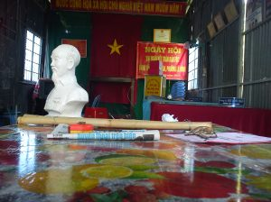 A bust of Ho Chi Minh, the Vietnamese flag and the stick of a local officer placed on his desk in an urban commune of the Mekong Delta. Source: the author, 2011.
