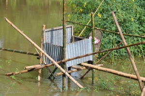 """A fishpond toilet over the water made of by bamboo sticks and metal scraps. One has to balance on the bamboo """"bridge"""" to be able to use the toilet. Source: Dunja Krause, 2012."""