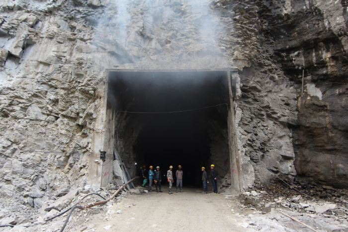 Nepali employees of the China Gezhouba Group Company waiting at the entrance of the headrace tunnel for the 60MW Trishuli 3A Hydropower Project. Dust from blasting and excavation inside rises above them. 2014. Photo by Austin Lord.